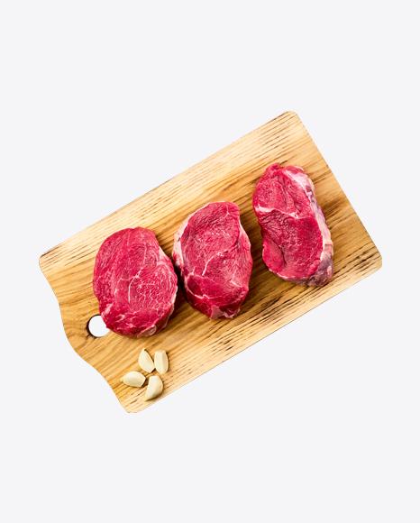 Raw Steaks w/ Garlic Cloves on Wooden Board